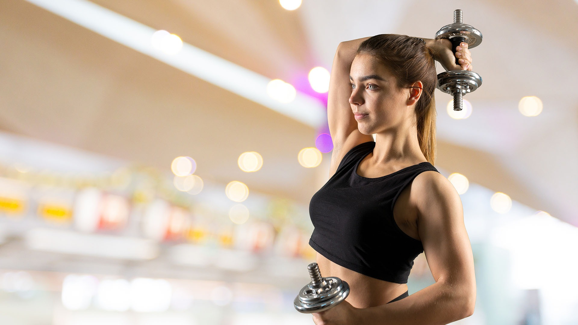 Studio close up photo of young woman lifting dumbbell